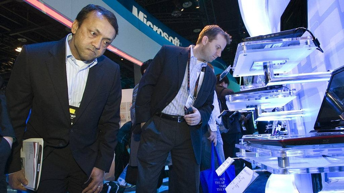 Ambrish Srivastava (L) and Daniel Rusbarsky of BMO Capital Markets look over Toshiba laptop computers in a Microsoft booth during the first day of the 2011 International Consumer Electronics Show (CES) in Las Vegas, Nevada January 6, 2011. The computers were showing glassless (no glasses required) 3D displays.