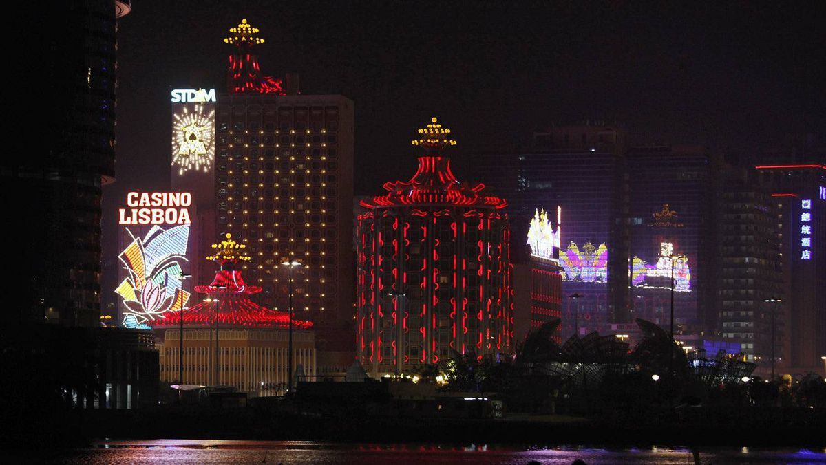 A couple walks on a waterfront in front of Casino Lisboa, owned by Sociedade de Turismo e Diversoes de Macau S.A.R.L. (STDM), in Macau on the evening of April 4, 2011.