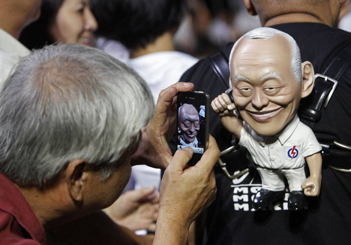 A man takes a picture of professional model maker Christopher Pereira, he carries a model of Singapore's Minister Mentor Lee Kuan Yew, during a People's Action Party (PAP) election rally in Singapore.