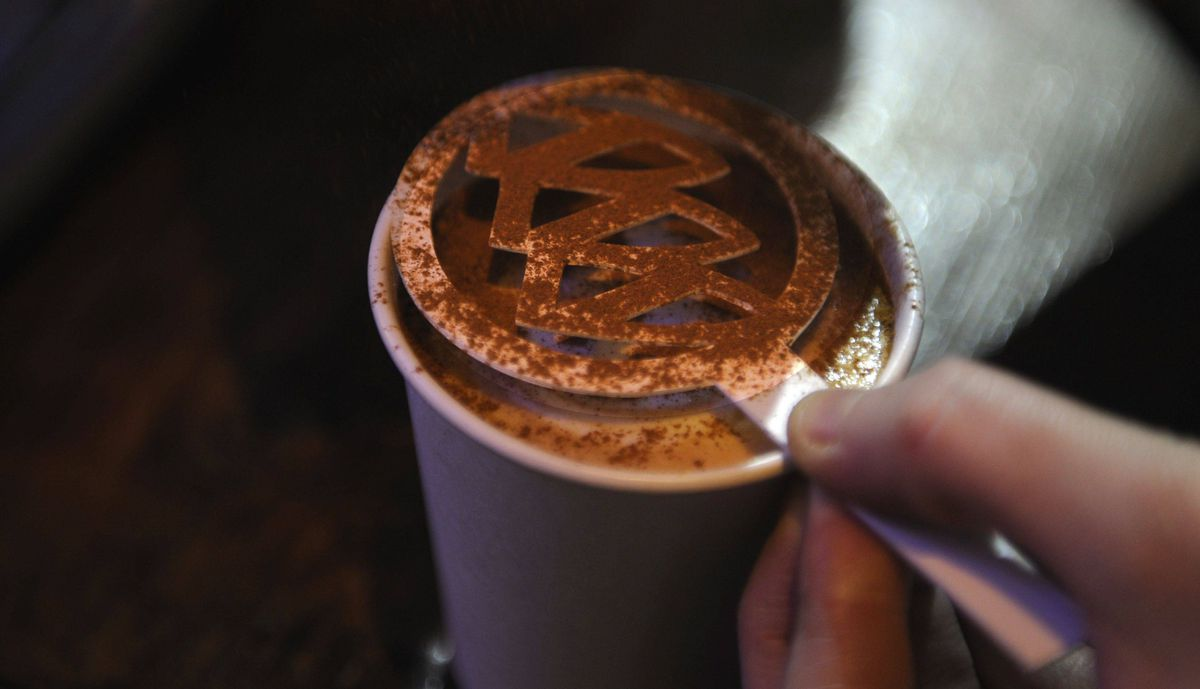 Barristas use cinnamon or hot chocolate to make Cadillac logo on espressos and cappuccinos during the media preview of the Canadian International Auto Show in Toronto.
