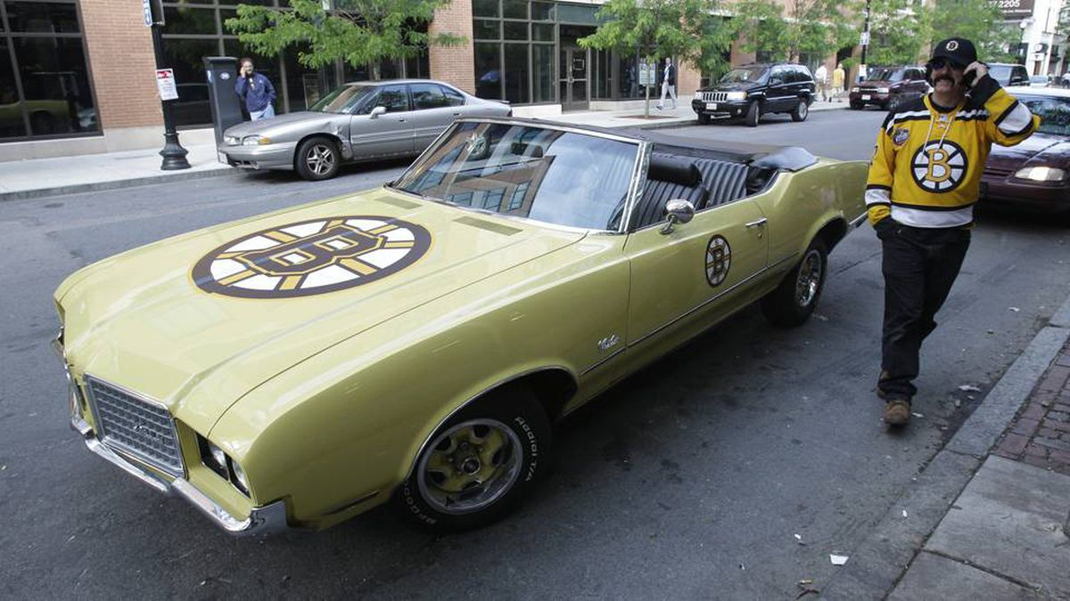 Steve Doran, of North Reading, Mass., stands beside his 1972 Oldsmobile Cutlass convertible outside the arena before Game 6.