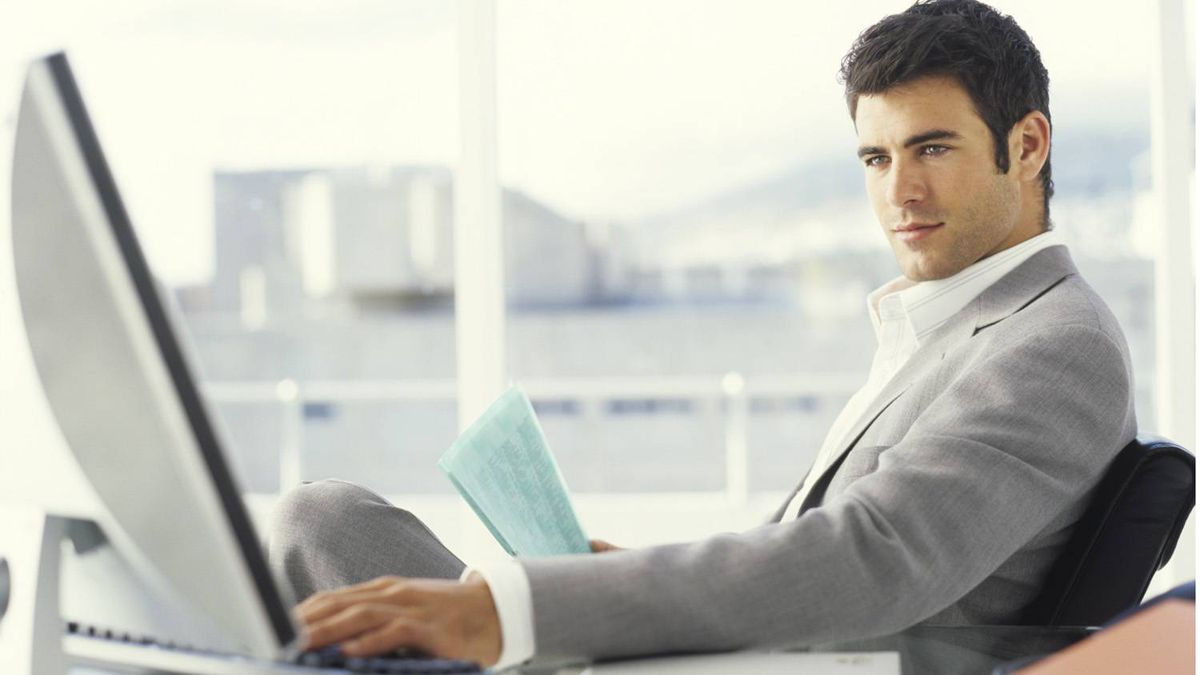 Young businessman using PC and holding documents, side view