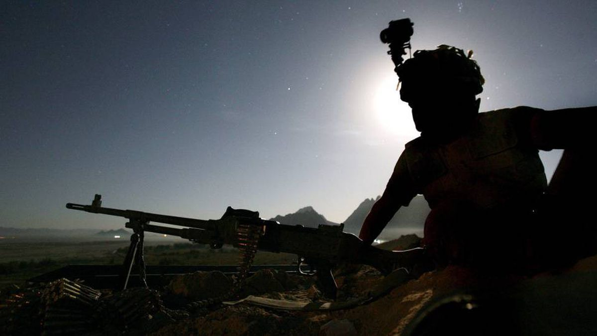 A soldier from A Company, second Princess Patricia's Canadian Light Infantry (2PPCLI), is silhouetted by the moon as he keeps night watch at Forward Operating Base Masum Gar in Panjwayi district, Kandahar province, 7 November 2006.
