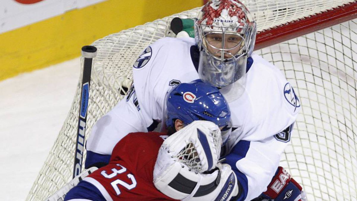 Montreal Canadiens' Mark Streit, from Switzerland, gets a glove in the face after sliding into Tampa Bay Lightning goaltender Karri Ramo during first period NHL hockey action Thursday, Jan. 3, 2008 in Montreal.