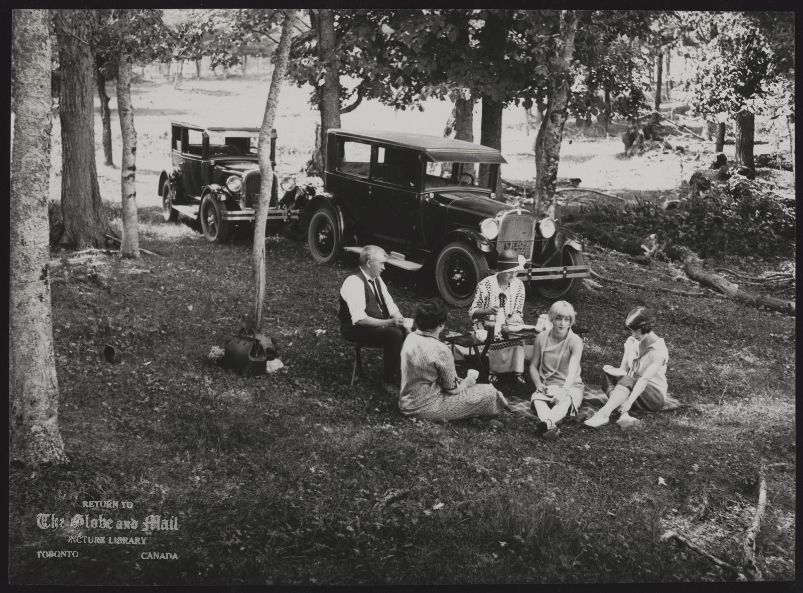 The notes transcribed from the back of this photograph are as follows: Neg. 25214-02 Picnic at roadside near Port Carling 1925.