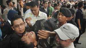 This file photo taken on November 25, 2011 shows security personnel evacuating a man after he collapsed while queueing for discounted BlackBerry smart phones at a mall in Jakarta.