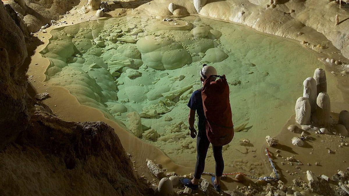 A researcher is shown in Lechuguilla Cave in Carlsbad Cavern National Park, with calcite formations shown in the background.