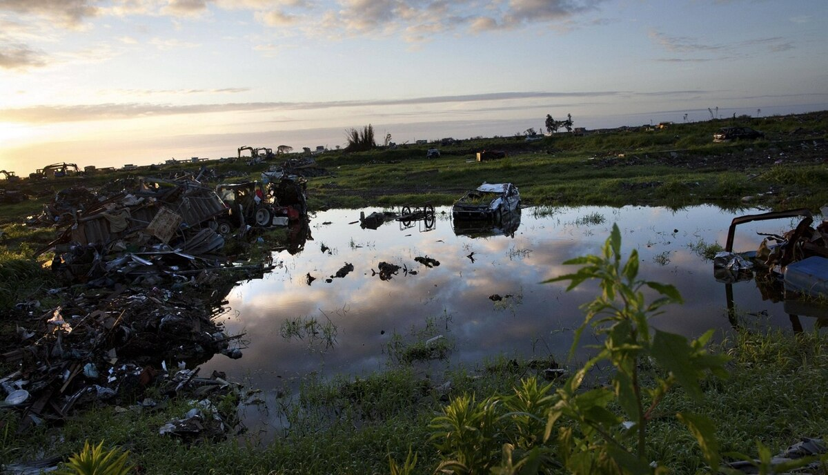 A car sits in a pool of water in what used to be a residential neighborhood in the town of Namie, inside the 20-kilometer exclusion zone around the Fukushima Daiichi nuclear plant July 24, 2011. A year after the Tsunami, cleanup has begun, but experts say areas inside the nuclear exclusion zone will be difficult to decontaminate.