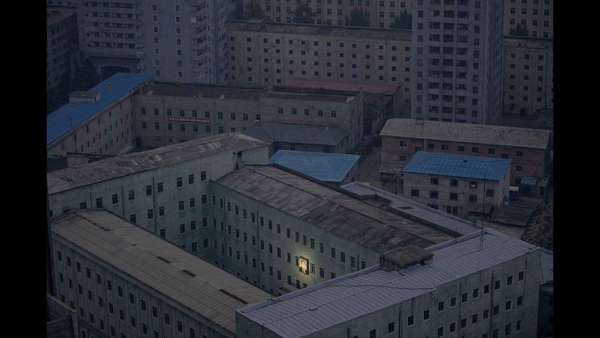 Damir Sagolj of Bosnia and Herzegovina, a Reuters photographer based in Thailand, has won the first prize Daily Life Singles with this photograph of a picture of North Korea's founder, Kim Il-sung, decorating a building in the capital Pyongyang October 5, 2011.