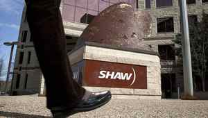 People walk past the headquarters of Shaw Communications in Calgary, Alta.,
