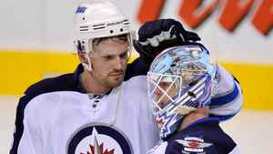 Winnipeg Jets defenceman Ron Hainsey (L) celebrates with goalie Chris Mason after they defeated the Carolina Hurricanes during NHL pre-season action in Winnipeg, September 28, 2011.
