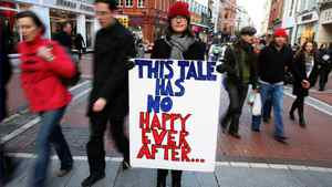 Berry Fleming, who lost her job, holds a placard in the main shopping area of Dublin, in November, 2010