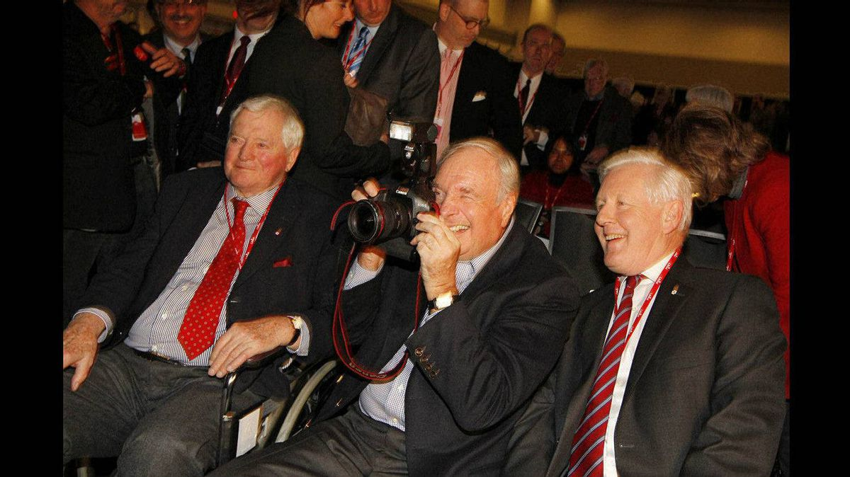 Former prime MInister Paul Martin plays with a photographer's camera before the welcoming ceremony and presidential candiates debate at the Liberal Convention in Ottawa. Former PM John Turner is left and interim Liberal leader Bob Rae is right.