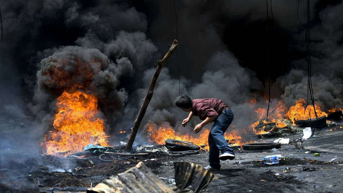 A Thai anti-government 'red shirt' protester throws wood onto a fire on a major Bangkok street during clashes May 17, 2010.
