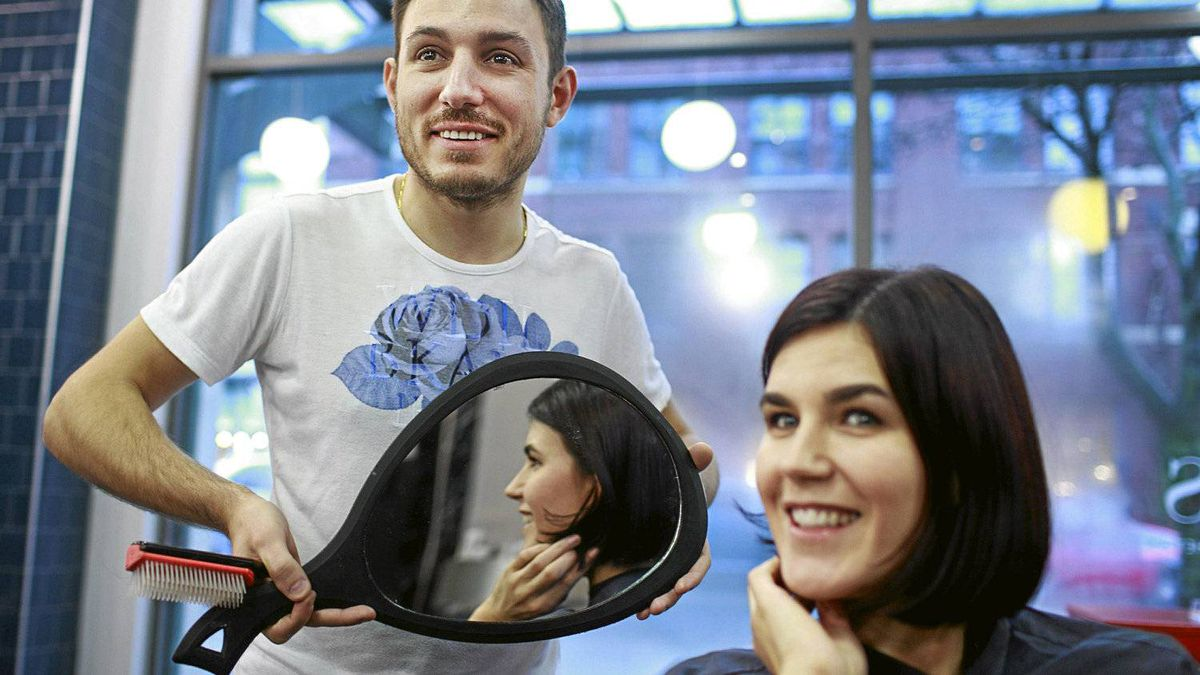 Opus hair salon owner Ludovic Jan shows his wife Jessica Jan her hair after giving her a trim at their salon in the Yaletown district of Vancouver, February 24, 2012.