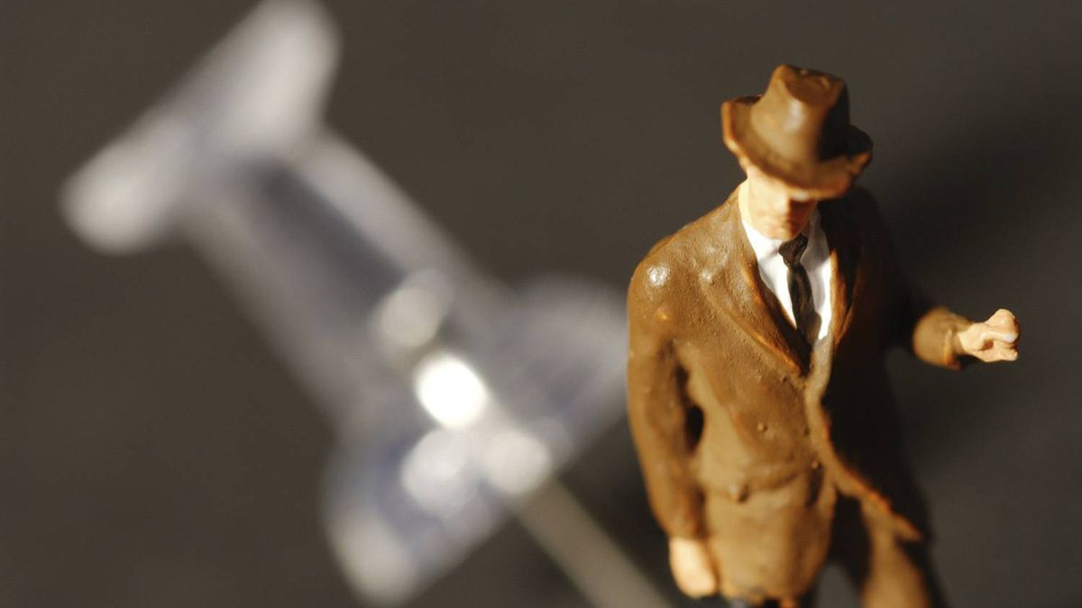 Miniature figure of retro salesman dodging push pin