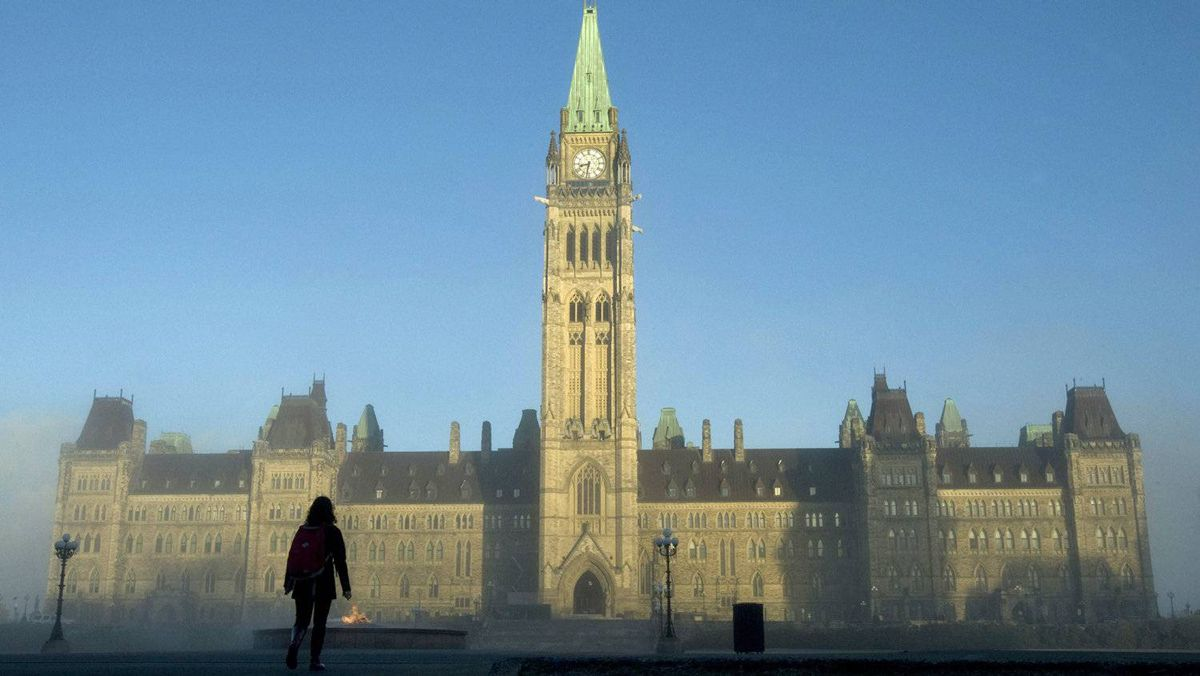 Sun illuminates the Peace Tower as a visitor makes their way to Parliament Hill on Nov. 3, 2010.