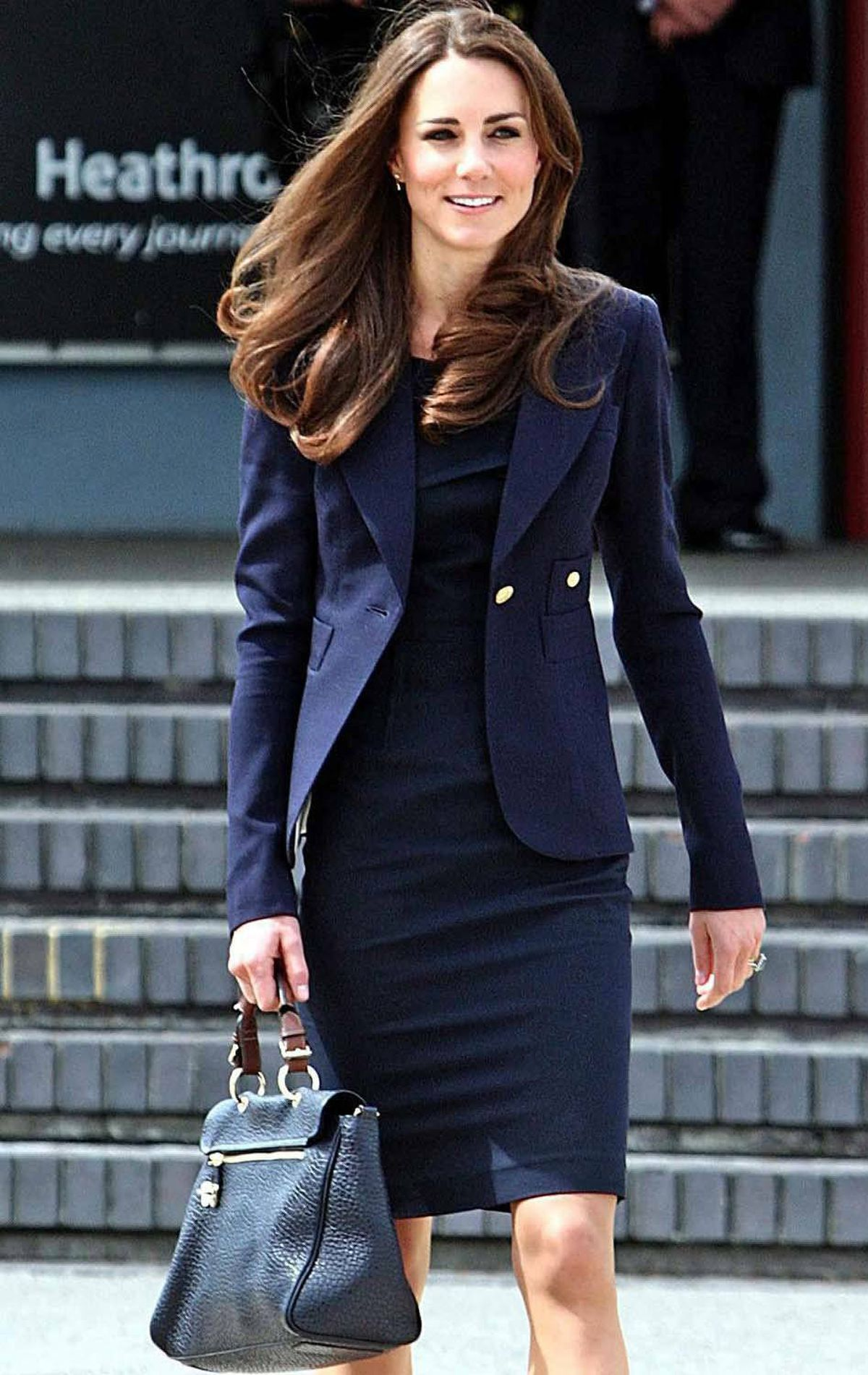 The newlywed leaves London's Heathrow Airport on June 30 in a business-like navy Roland Mouret dress.
