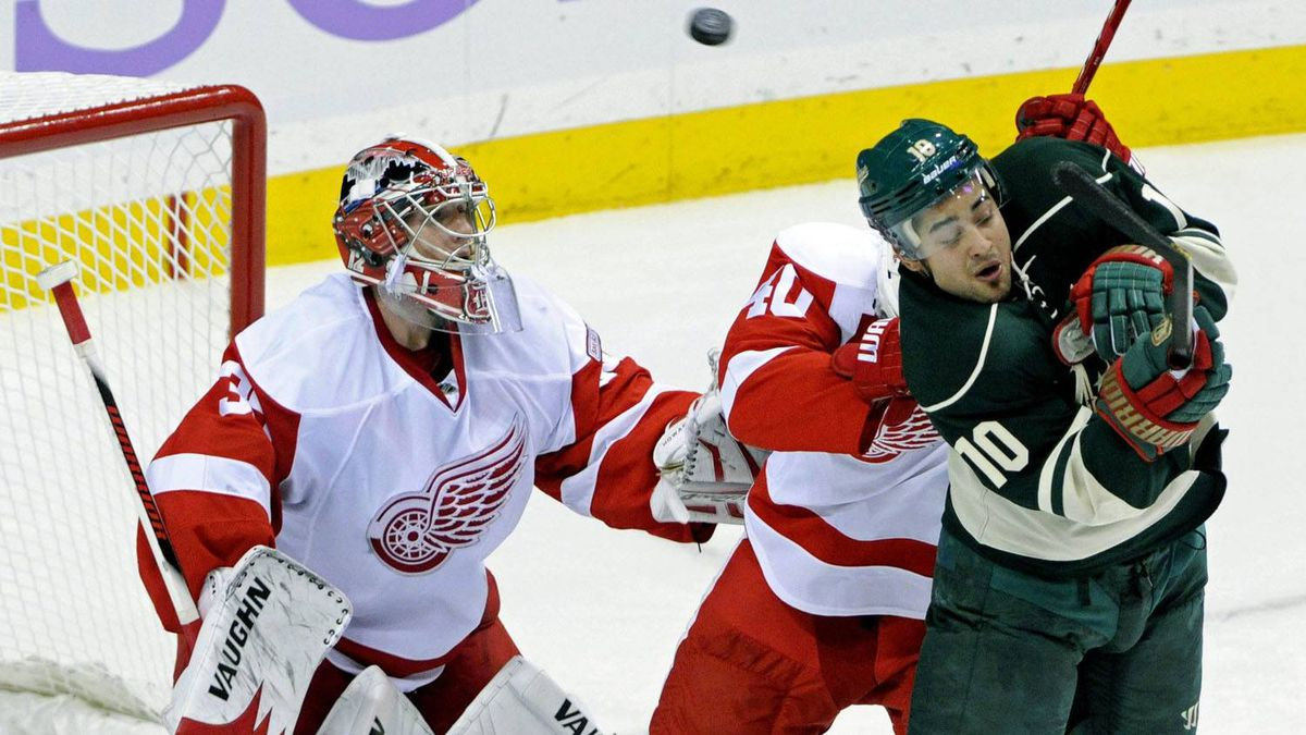 Minnesota Wild's Devin Setoguchi (10) ducks away as a high-flying puck zooms past him and over Detroit Red Wings goalie Jimmy Howard (35) in the third period of an NHL hockey game, Saturday, Oct. 29, 2011, in St. Paul, Minn. The Wild won 1-0. (AP Photo/Jim Mone)