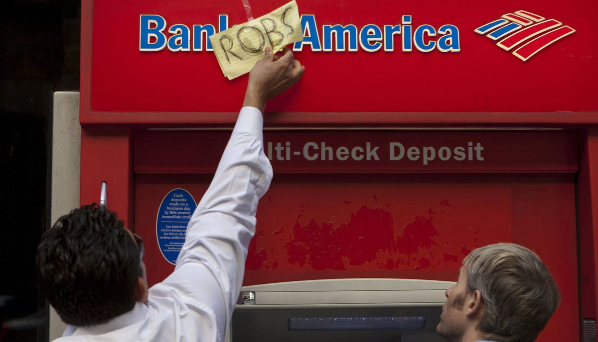 A bank employee peals off a sign left by demonstrators on a bank teller, as part of the Occupy Wall Street movement protests, Thursday, Oct. 6, 2011.