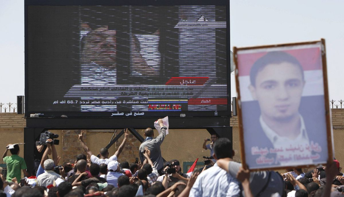 A poster with a picture of a man who was killed during the revolution is carried as Egypt's ousted President Hosni Mubarak is seen on a TV screen as he enters the courtroom on a hospital bed, outside the Police Military Academy complex in Cairo, Egypt .