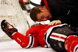Chicago Blackhawks' Brian Campbell, left, talks to a team trainer after being knocked down by Washington Capitals' Alex Ovechkin during the first period of an NHL hockey game in Chicago, Sunday.