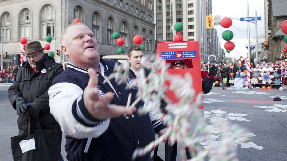 Mayor Rob Ford throws candy into the crowds during the 107th annual Santa Claus Parade