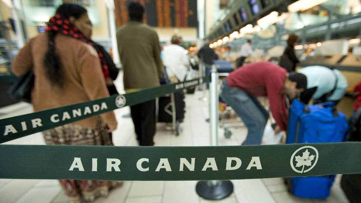 Air Canada passengers check in at Vancouver's airport on June 17, 2008.