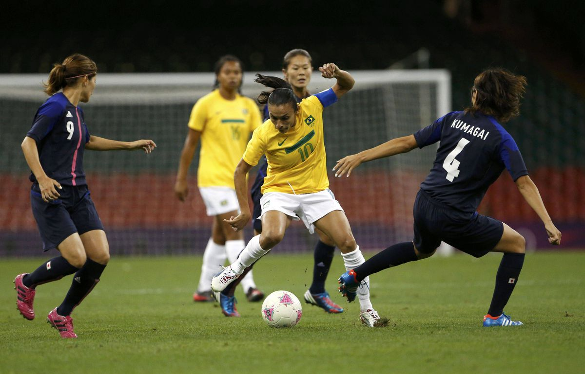 Brazil's Marta drives the ball through Japan's Kawasumi and Kumagai.