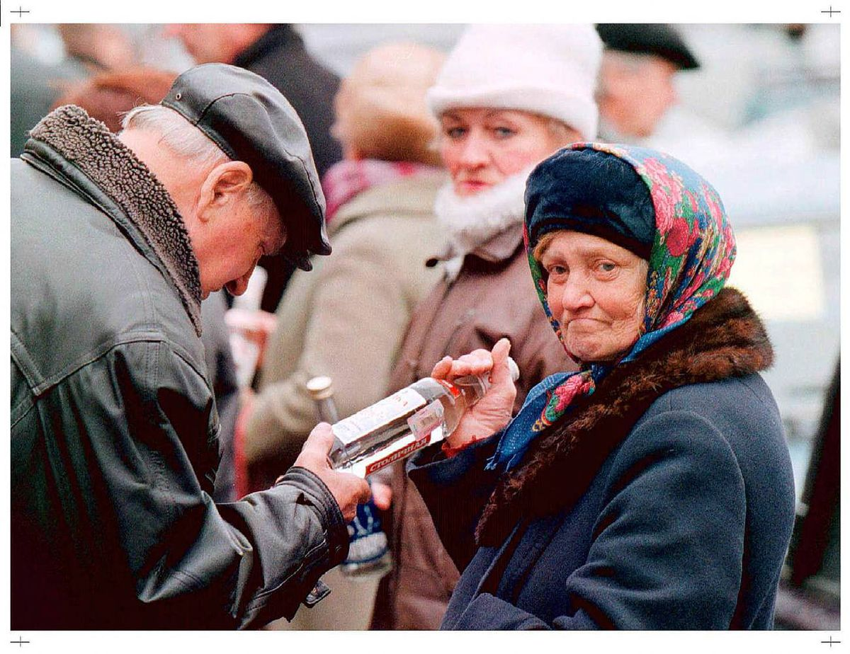 An elderly Russian woman illegally sells vodka on a street, as she keeps a look-out for any police in downtown Moscow, Tuesday, Nov. 3, 1998. Many elderly people sell goods in the streets trying boost their income. (AP Photo/Ivan Sekretarev )