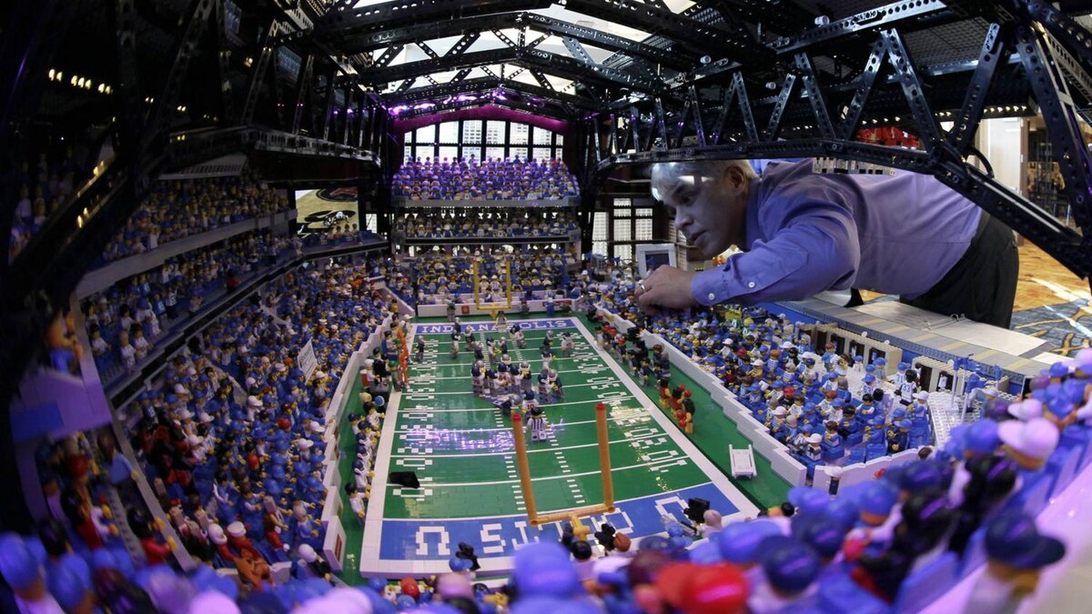 Brian Alano adjusts a piece in his Lego scaled replica of Lucas Oil Stadium which is on display at the Super Bowl XLVI media center Wednesday, Feb. 1, 2012, in Indianapolis. Alano spent three years and used over 30,000 pieces to build the model. The New England Patriots will face the New York Giants in Super Bowl XLVI on Feb. 5. (AP Photo/David J. Phillip)