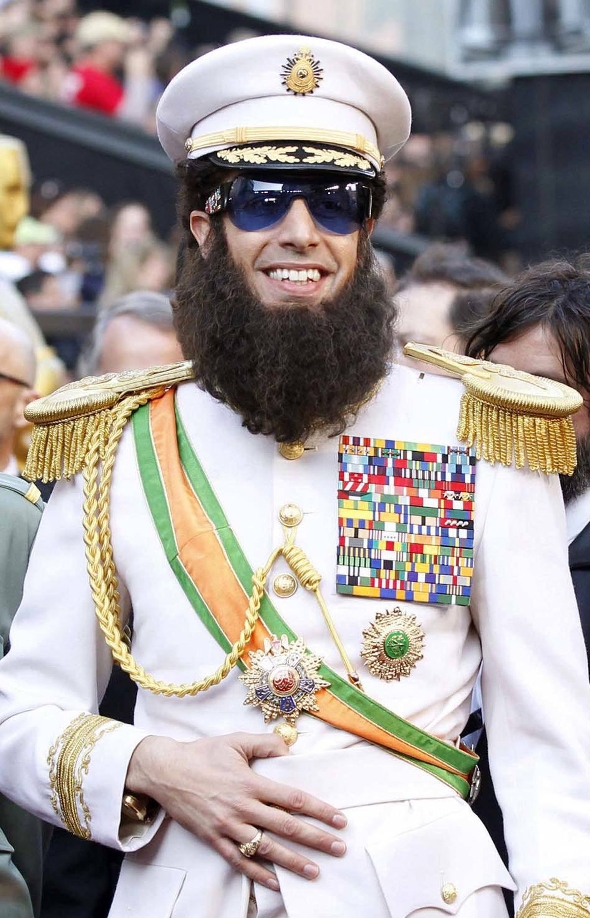 After playing a stereotypical Kazakh dolt and a stereotypical gay Austrian fashion reporter, Sacha Baron Cohen comes up with an entirely new idea for a movie: playing a stereotypical North African despot. Here he is in character on the Oscars red carpet on Sunday.
