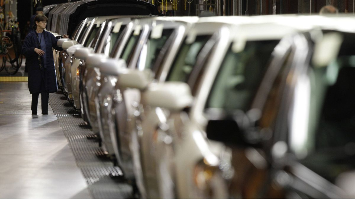 A line worker checks vehicles at a General Motors assembly plant in Hamtramck, Mich.
