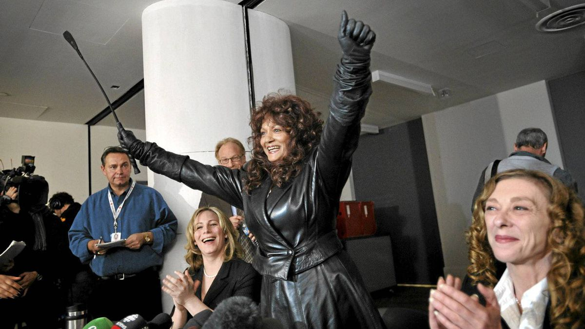 Left to right sex worker advocate Terri-Jean Bedford raises her arms in victory during a press conference in Toronto, Ont. Monday, March 26, 2012. Ontario,ÄöaÑa¥s top court has legalized brothels in a ruling that came out today.