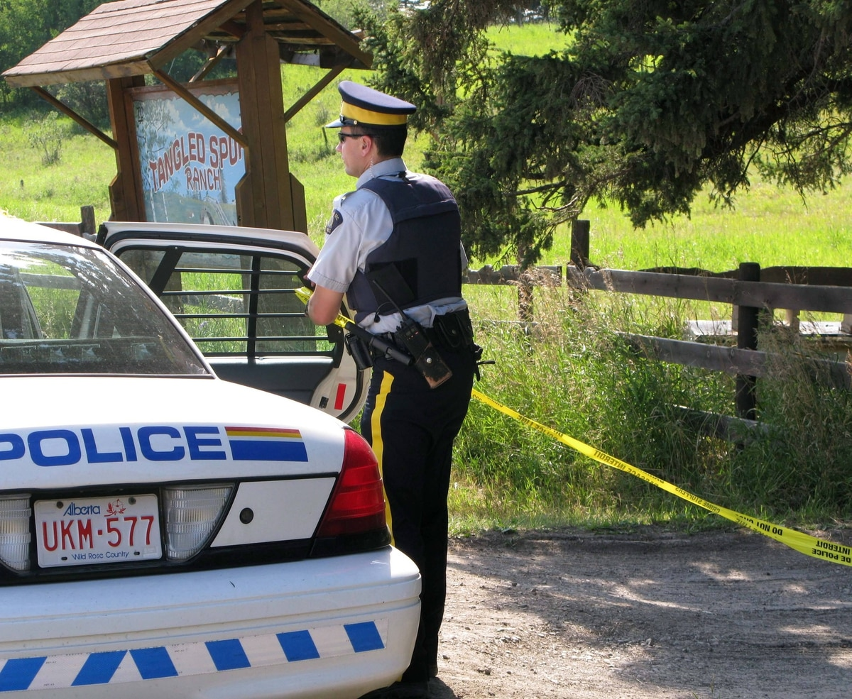 An RCMP officer puts up police tape near a rural residence south of Calgary, Friday, Aug. 10, 2012. A peace officer who attended the acreage near Priddis, Alta. was transported to hospital where he later died.