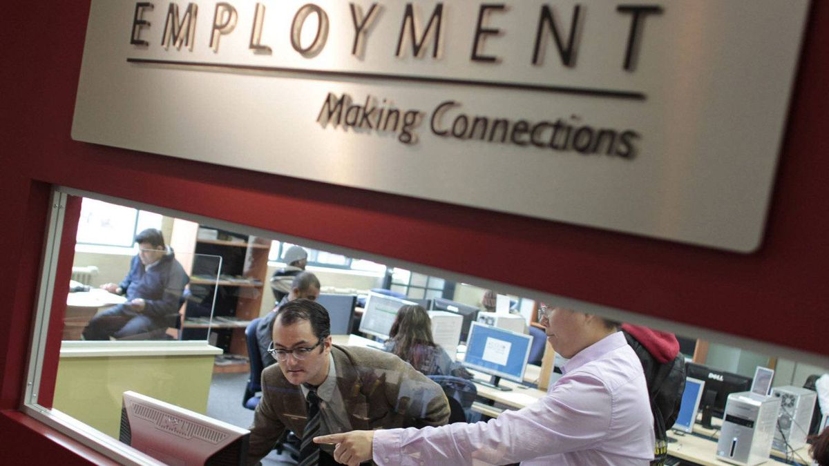 Andrew Anastasovski, 31, is assisted by employment consultant Quoc Phan, right, on Oct. 18, 2011, while preparing his resume at one of the five ACCES Employment locations in the Greater Toronto Area.