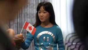 Mengyi Fu, 10 receives, a Canadian flag as her parents Jing Shan Fu and mom Mao Qiong Lin watch during a Canadian Citizenship ceremony in Ottawa on Sept. 29, 2010.
