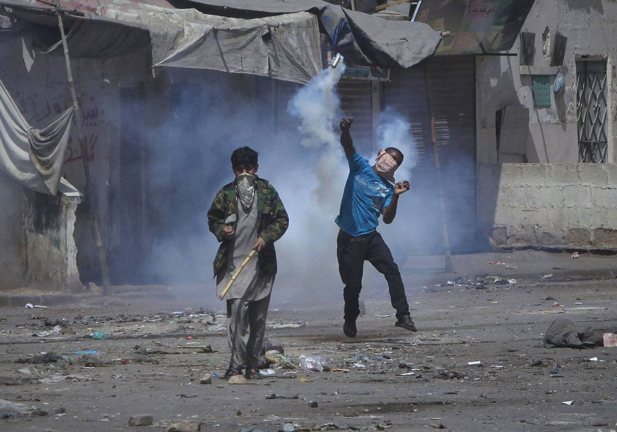 A protester throws a teargas shell back towards security forces as they arrive for an operation in the Lyari area of Karachi March 23, 2012. Residents of Karachi's Lyari area protested on Friday against the raid operations of the law enforcement agencies.