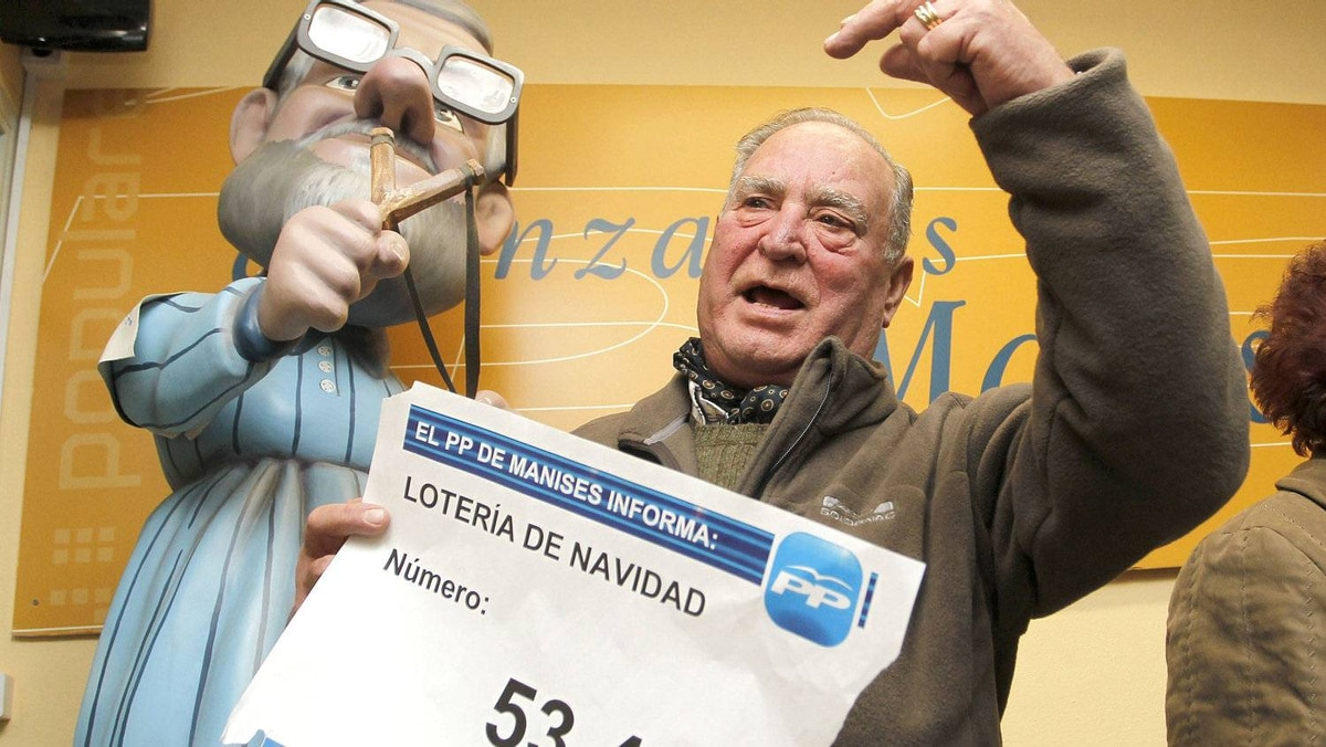 A member of the People's Party (Partido Popular) celebrates winning the second prize of Spain's Christmas lottery 'El Gordo' next to a figure of Spain's Prime Minister Mariano Rajoy, in Manises, near Valencia, Dec. 22, 2011.