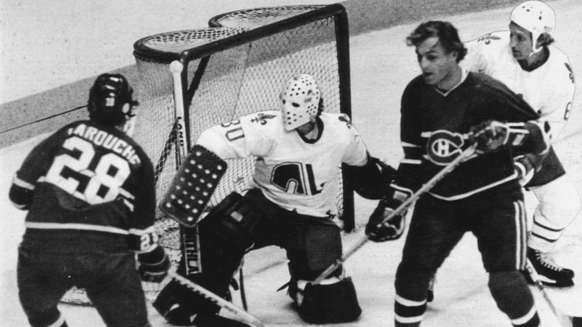 In spite of a continuous attack by Montreal Canadiens Guy Lafleur and Pierre Larouche, Quebec Nordiques goalie Michel Dion holds his ground in a Quebec City game in 1979.