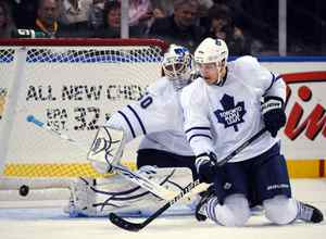 Caption: Toronto Maple Leafs goaltender Jonas Gustavsson (L) looks down to the puck as defenseman Luke Schenn defends during first period NHL hockey action against the Buffalo Sabres in Buffalo, New York, October 30, 2009. REUTERS/Gary Wiepert