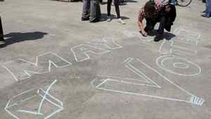 Jeff Werkmeister writes a message on the ground at a pre-election gathering in London, Ont., Saturday, April 30, 2011.