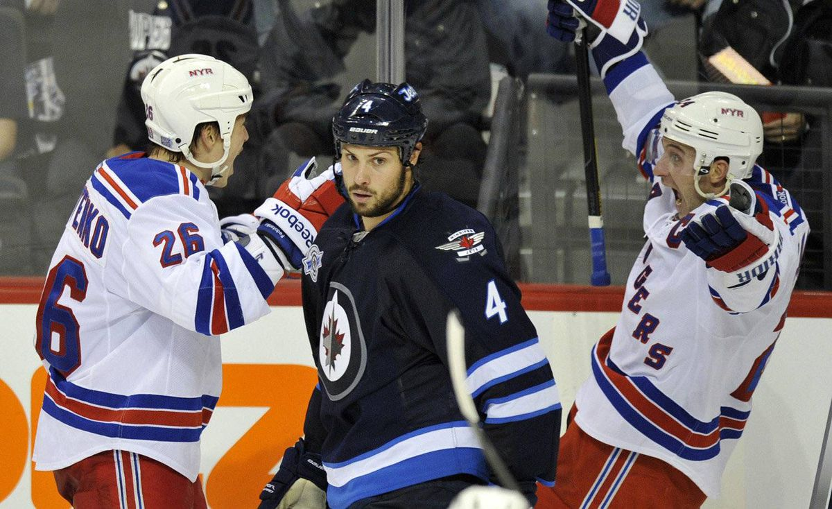 New York Rangers' Ryan Callahan (R) celebrates his game-winning goal with Ruslan Fedotenko (L) as Winnipeg Jets' Zach Bogosian skates to the bench during the third period of their NHL game in Winnipeg, October 24, 2011.