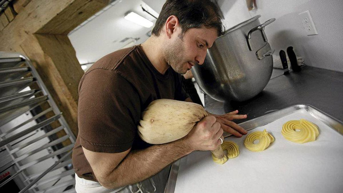 He scoops the dough into a pastry bag, and then pipes it into tidy rounds.