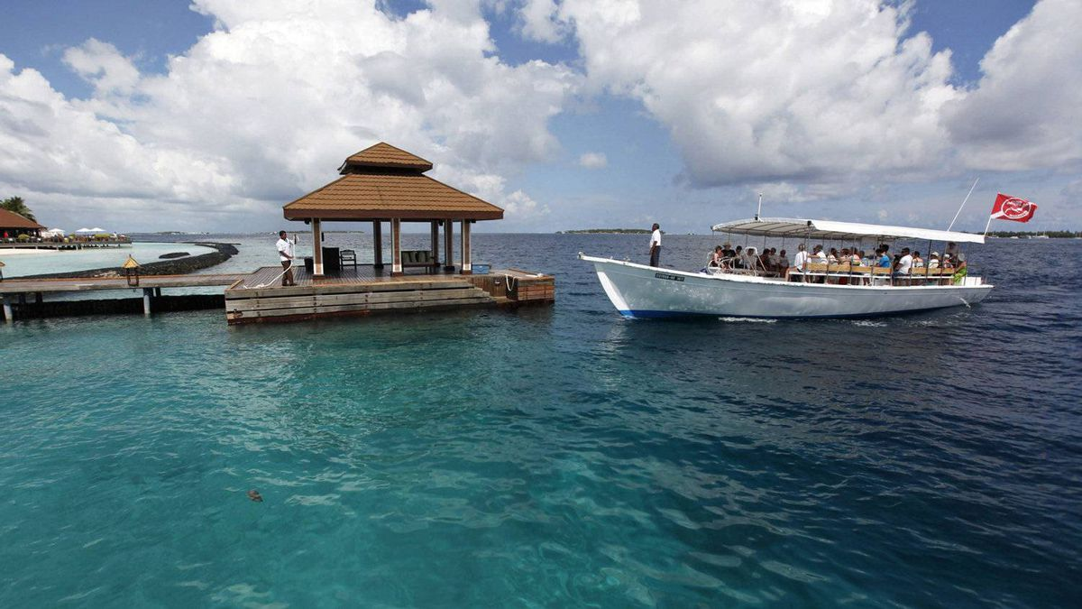 A boat with foreign tourists aboard arrives in a resort jetty in Kurumba island in Maldives.