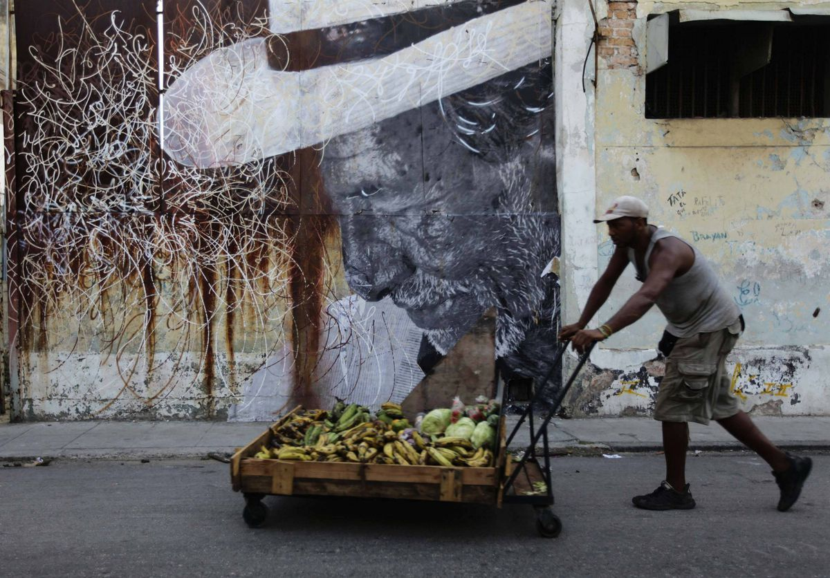 A vegetable seller pushes his cart past a creation by Cuban-American artist Jose Parla and French artist J.R. on a building wall in Havana.