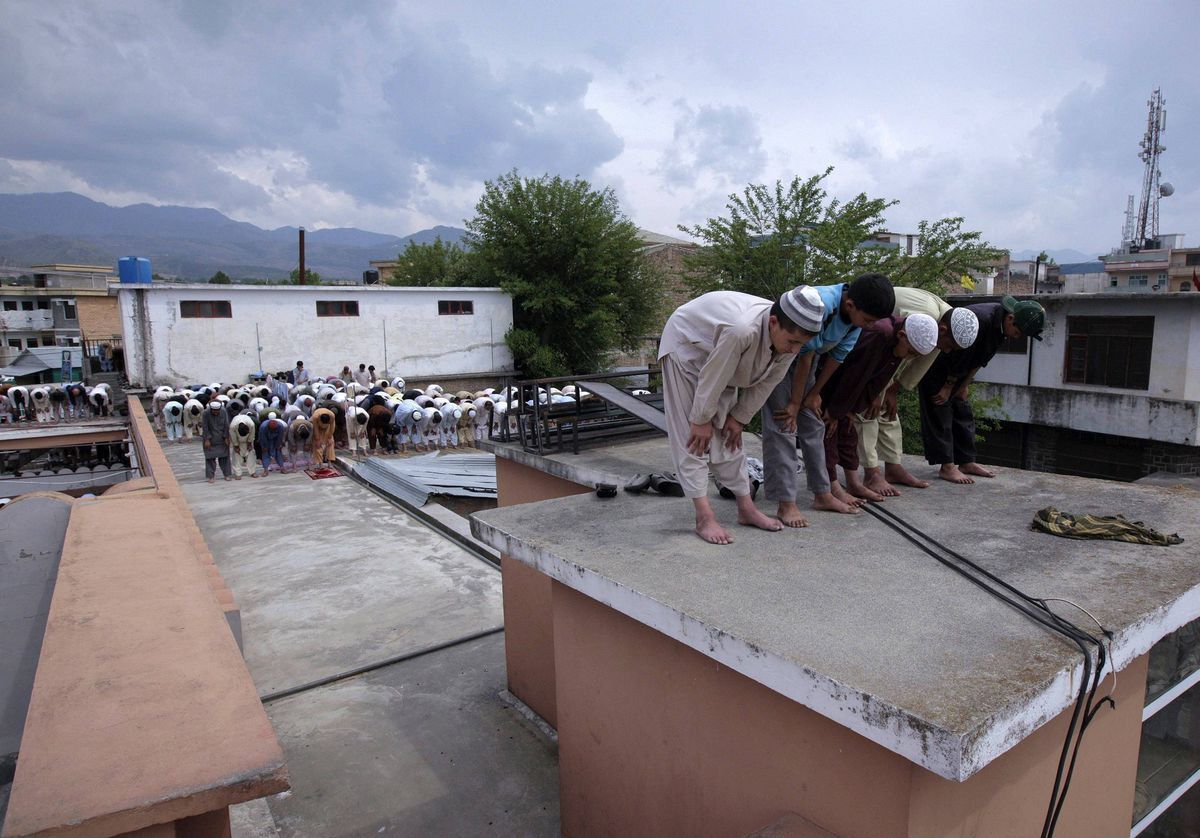 Residents offer Friday prayers on the roof of Jamia Masjid Mandian in Abbottabad, Pakistan.