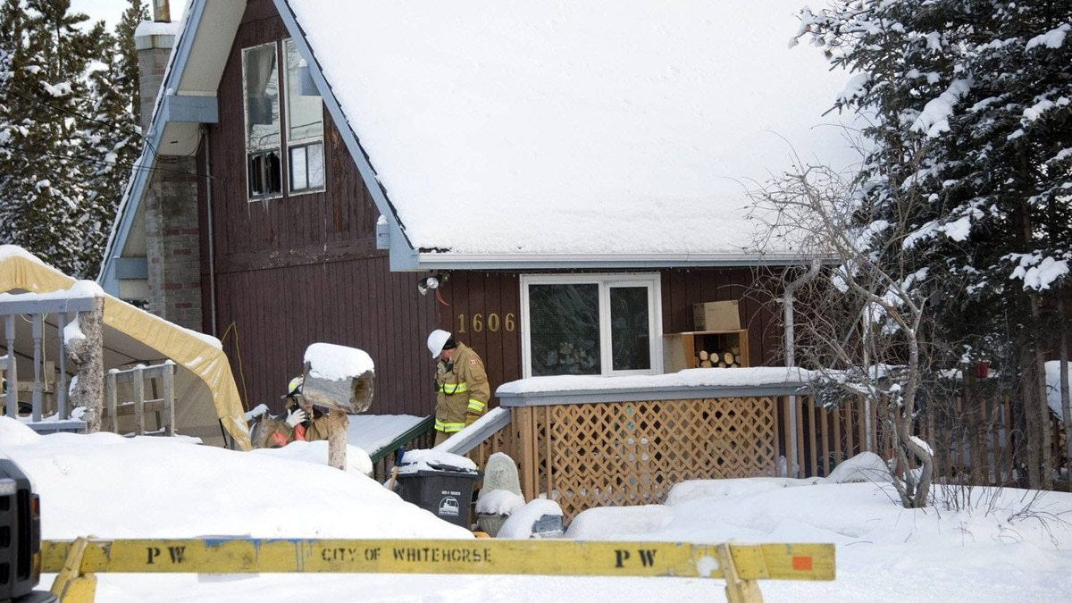 Firefighters examine the scene outside a house in Whitehorse, Jan.30, 2012, where the bodies of five people, including two school-aged children, were found Sunday morning.