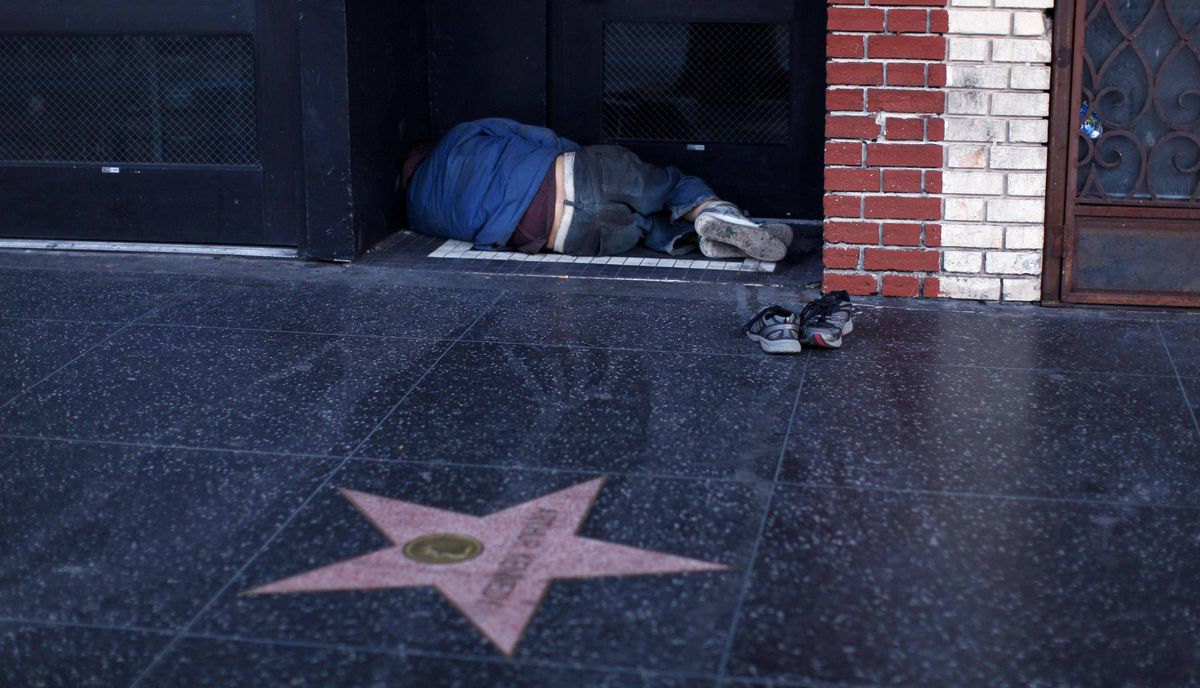 A homeless man sleeps in a doorway in the early morning hours along Hollywood Boulevard in Hollywood, California February 22, 2012.