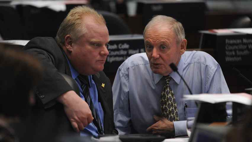 Toronto mayor Rob Ford converses with deputy mayor Doug Holiday during debate over the LRT transit issue at Toronto city hall on March 21, 2012.